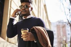 Afrikansk amerikanstudent av affärsskolan som kallar till kollegan som diskuterar idérika idéer för projekt genom att använda mob Arkivbild
