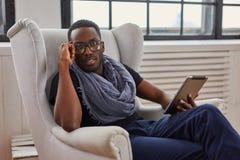 Afrikansk amerikanstudenten sitter på en stol och att använda en minnestavlaPC Royaltyfri Fotografi