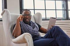 Afrikansk amerikanstudenten sitter på en stol och att använda en minnestavlaPC Royaltyfria Bilder