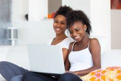 Afrikansk amerikanstudentflickor som använder en bärbar datordator - svart p Royaltyfri Foto