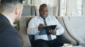 Afrikansk amerikantimme-chef som har jobbintervju med den unga mannen i dräkt och håller ögonen på hans meritförteckningapplikati arkivfilmer