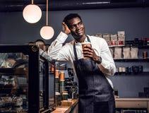 Afrikansk barista som rymmer en kopp med kaffe, medan luta på en räknare i en coffee shop och se från sidan royaltyfri bild