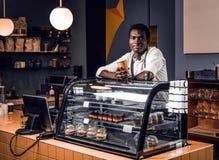Afrikansk barista som rymmer en kopp med kaffe, medan luta på en räknare i en coffee shop och se en kamera arkivfoton