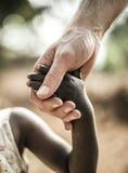 Afrikansk childshand som rymmer en vit vuxen människahand Fotografering för Bildbyråer