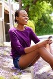 Afrikansk dam som använder mobiltelefonen Arkivfoton