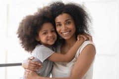 Afrikansk ensamstående mamma- och barndotteromfamning som ser kameran royaltyfri fotografi
