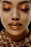 Afrikansk etnisk kvinnlig framsida för guld- lyxig svart hudkvinna Ung afrikansk amerikanmodell med smycken royaltyfri bild