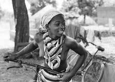 Afrikansk flicka med en cykel Arkivbild