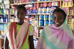 Afrikansk flickaförsäljare för två barn i kemikalieer för ett shoppahushåll Arkivfoto