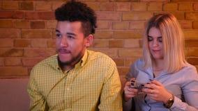 Afrikansk grabb med hans blonda caucasian flickvänlekvideogame med styrspaken uppmärksamt i hemtrevligt hem stock video