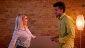 Afrikansk grabb och blond caucasian flicka som dansar aktivt att flörta med de i romantisk och hemtrevlig atmosfär stock video
