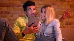 Afrikansk grabb och caucasian flicka som hemma sitter på soffan som har en video appell på minnestavlan som den är glad lager videofilmer