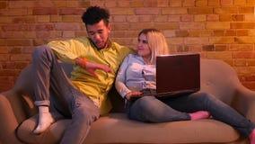Afrikansk grabb och caucasian flicka som sitter på soffan med bärbara datorn och joyfully hemma flörtar med de lager videofilmer