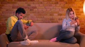 Afrikansk grabb och caucasian flicka som sitter på soffan som uppmärksamt hemma håller ögonen på in i deras smartphones stock video