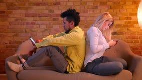 Afrikansk grabb och caucasian flicka som tillbaka sitter för att dra tillbaka på soffan som hemma håller ögonen på in i smartphon lager videofilmer
