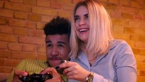 Afrikansk grabb och hans blonda caucasian flickvänlekvideogame och att ge hemmastadda fem till varandra arkivfilmer