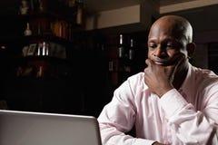Afrikansk grabb på bärbar dator arkivfoto