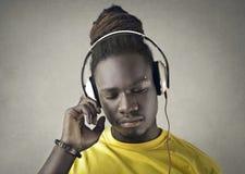 Afrikansk grabb som lyssnar till musik med hörlurar arkivfoto
