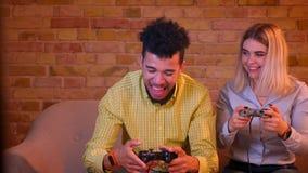 Afrikansk grabb som spelar videogamen mot hans flickvän och segrar som är lyckliga och tillfredsställda i hemtrevligt hem arkivfilmer