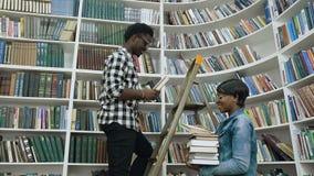 Afrikansk grabb som väljer böcker från hyllorna, medan stå på stege och ge böcker till den afrikanska flickan i universitet arkivfilmer