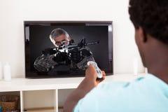 Afrikansk hållande ögonen på television för ung man Arkivfoto