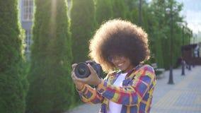 Afrikansk kvinna för stående med en afro frisyrfotograf med en kamera på det stads- landskapet stock video