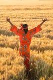 Afrikansk kvinna i traditionell kläder som står i ett fält av skörden Arkivfoton