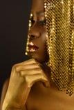 Afrikansk kvinna med det guld- metalliska sminket och fulla skinande kanter, slut upp Royaltyfri Fotografi