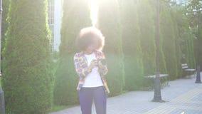 Afrikansk kvinna med en afro frisyrfotograf med en kamera på det stads- landskapet arkivfilmer