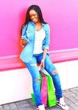 Afrikansk kvinna med shoppingpåsar genom att använda smartphonen i stad royaltyfri bild