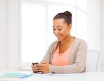 Afrikansk kvinna med smartphonen i regeringsställning Arkivfoto