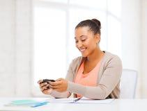 Afrikansk kvinna med smartphonen i regeringsställning Arkivfoton