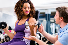 Afrikansk kvinna och instruktör på övningen i idrottshall Royaltyfri Fotografi