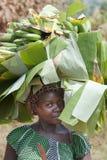 Afrikansk kvinna som bär tunga påfyllningar på huvudet Fotografering för Bildbyråer
