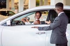 Afrikansk kvinna som förvånas av den nya bilen, gåva för min härliga fru Arkivfoton