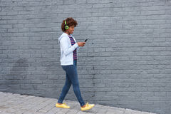Afrikansk kvinna som går och lyssnar till musik på mobiltelefonen Royaltyfri Fotografi