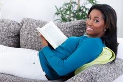 Afrikansk kvinna som kopplar av med en bok Arkivfoton