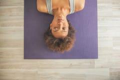 Afrikansk kvinna som ligger på en matt yoga arkivbilder