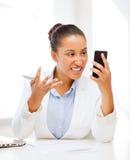 Afrikansk kvinna som ropar in i smartphonen Arkivfoton