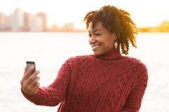 Afrikansk kvinna som tar selfie fotografering för bildbyråer