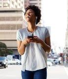 Afrikansk kvinna som tycker om lyssnande musik på hennes mobiltelefon arkivbild