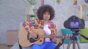 Afrikansk kvinnablogger med en afro frisyr med en gitarr för kameran lager videofilmer