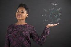 Afrikansk kvinnainnehavhand ut med ett jordklot för lopp på svart tavlabakgrund arkivfoto