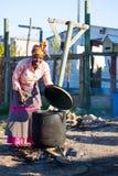 Afrikansk kvinnakockmat i stor svart kruka. Arkivfoto