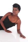 Afrikansk kvinnlig i svart klänning som ner lägger Fotografering för Bildbyråer