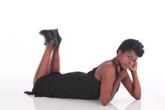 Afrikansk kvinnlig i svart klänning som ner lägger Arkivfoton