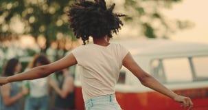 Afrikansk ladie med closeupen för lockigt hår på picknicken som framme spelar av kamerabanhoppningen och, har en rolig tid 4K sak lager videofilmer