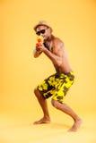 Afrikansk man i swimwearskytte med vattenvapnet Fotografering för Bildbyråer