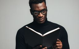 Afrikansk man med en bok arkivbild