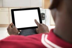 Afrikansk man som använder den Digital minnestavlan royaltyfria bilder